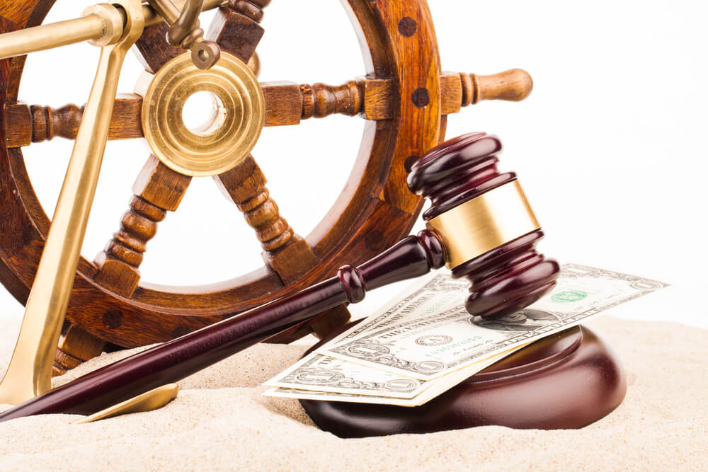 Gavel and ship steering wheel set over Maritime Law paper